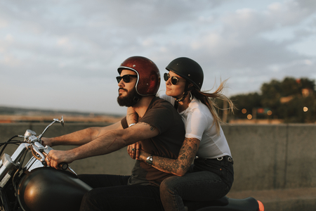 Biker couple riding down the road in the sunset Stock Photo