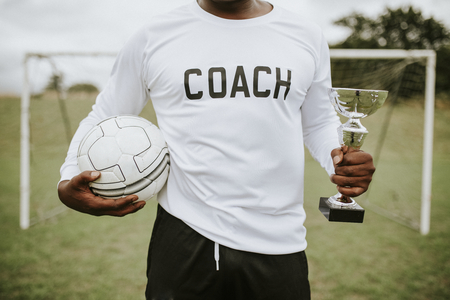 Soccer coach holding a trophy cup and ball