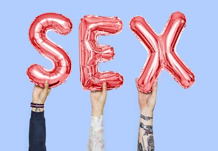 Mani che tengono la parola in lettere a palloncino