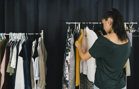 Model picking an outfit from the clothing rack