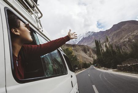 車の窓から涼しい風を楽しむ女性