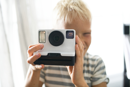 Blond boy taking an instant photo Фото со стока