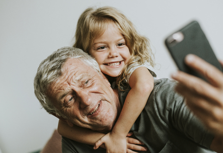 Grandfather taking a selfie with his granddaughter