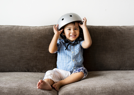 Little boy sitting on a sofa and wearing a helmet