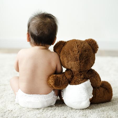 Detrás de un bebé con un osito de peluche Foto de archivo