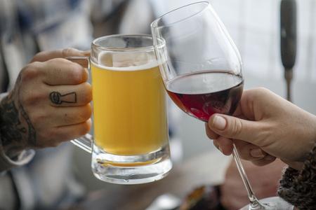 Freunde jubeln bei Wein und Bier Standard-Bild