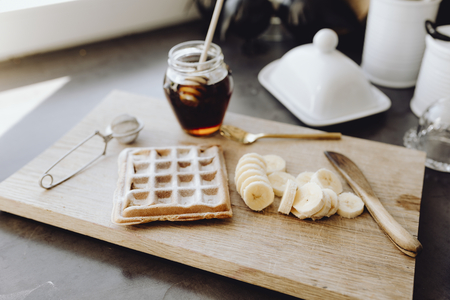 Waffle and slices of banana on a wooden tray next to a honey jar