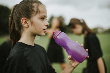 Giocatrice di football femminile che beve da una bottiglia d'acqua