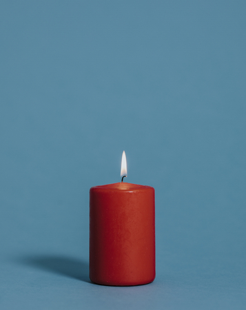 Burning candle in red color Stock Photo
