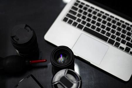 Closeup of a camera lens and a laptop Banco de Imagens - 115868924
