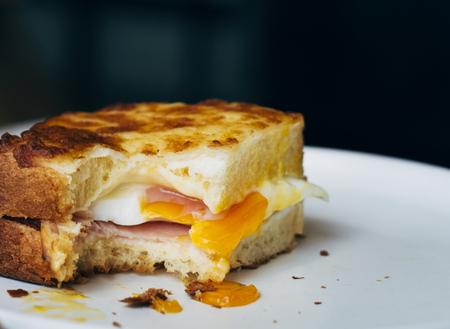 Bitten egg sandwich on a plate Stock Photo