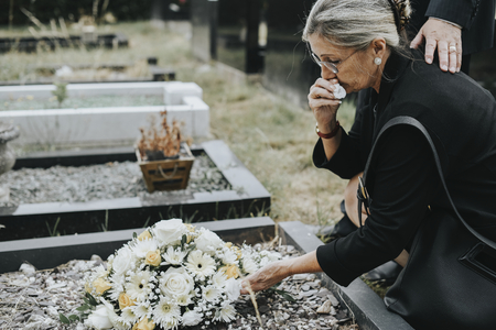 Old woman laying flowers on a grave Stock Photo - 115868962