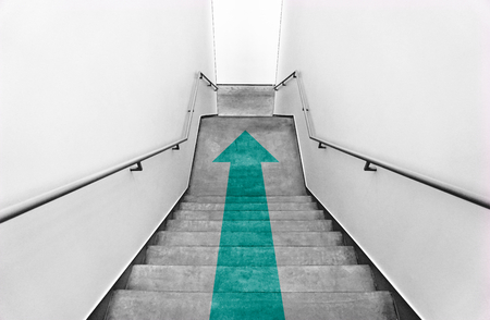 Green arrow on a staircase Imagens