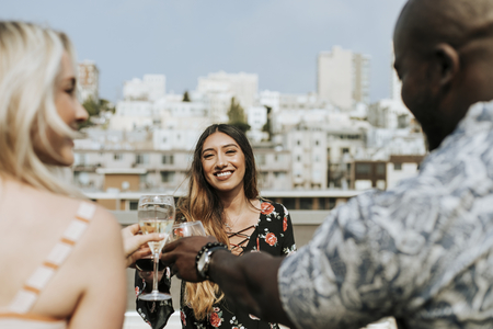 Cheerful friends toasting at a rooftop party Stock Photo