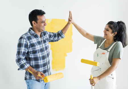 Couple giving a high five while renovating their new house