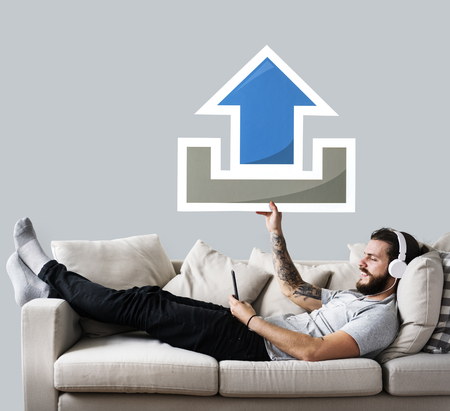 Male on a couch holding an upload icon Stock Photo