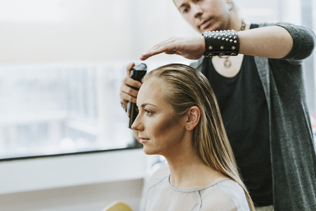 Model getting her hair done by a stylist