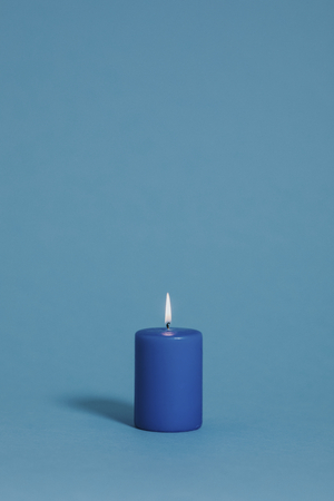 Burning candle in blue color Stock fotó