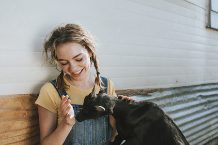 Happy young woman playing with a black baby goat