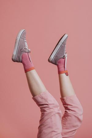 Vrouwenbenen in roze broek in de lucht Stockfoto