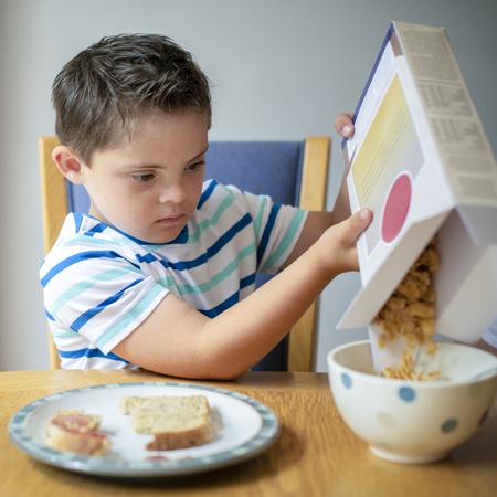 Garçon versant des cornflakes dans un bol Banque d'images