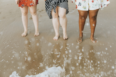 Diverse women soaking their feet in the water Stock Photo - 115871936