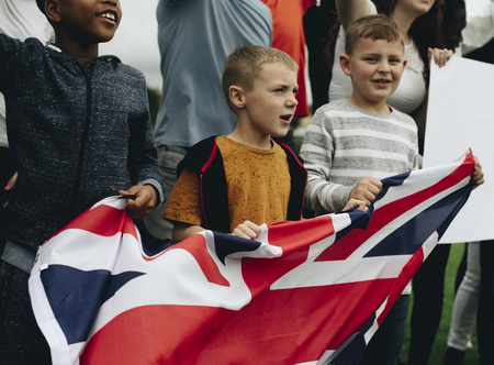 Group of diverse kids showing a UK flag in a protest