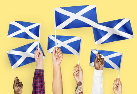 Hands waving flags of Scotland Banque d'images - 115871968