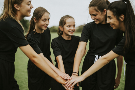 Young rugby players stacking hands together Stock fotó - 115871969