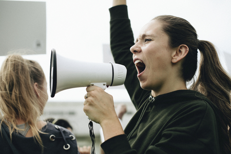 Female activist shouting on a megaphone Stockfoto - 115870071
