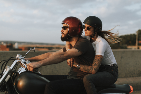 Biker couple riding down the road in the sunset Imagens