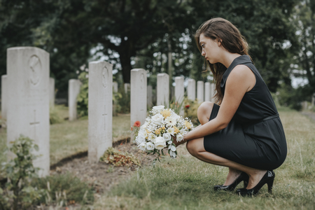 Young widow laying flowers at the grave 写真素材