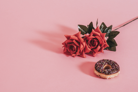 Tasty glazed donut beside a rose Фото со стока