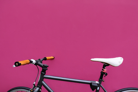 Black city bicycle on pink background