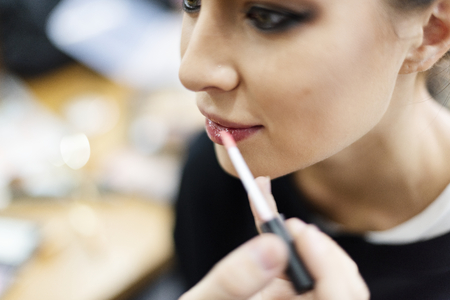 Makeup artist applying lip gloss onto model Stock Photo