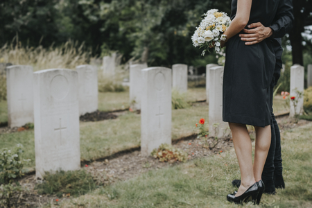 Couple standing together by a gravestone Imagens