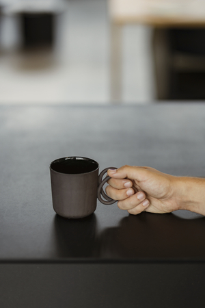 Hand holding a black coffee cup on a black table