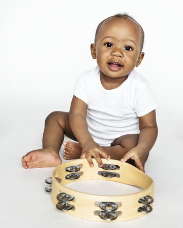 Baby sitting on the floor with a tambourine Stock Photo