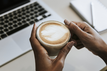 Woman drinking a cup of coffee while working