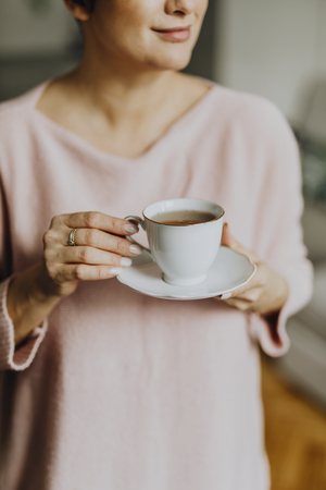 Happy woman enjoying a warm cup of tea for breakfast Banco de Imagens