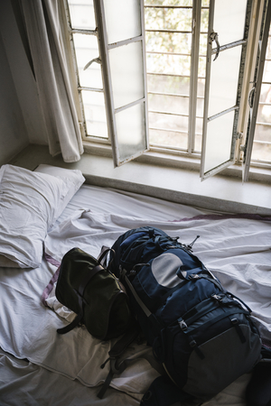 Backpack on a bed in a hotel room in the morning