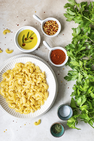 Dry pasta in a bowl surrounded by fresh ingredients