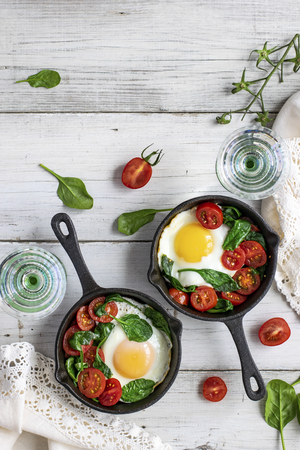 Freshly cooked eggs and tomatoes in a skillet Фото со стока