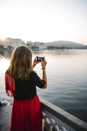 Western woman capturing the view of Udaipur city, India Stock Photo - 116689574