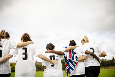 Female football players huddling and walking together Stok Fotoğraf