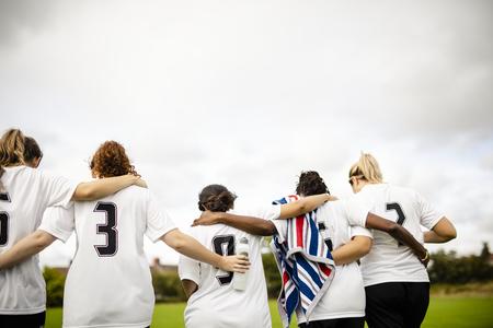 Female football players huddling and walking together Фото со стока