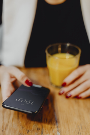 Woman having a glass of juice and checking her phone