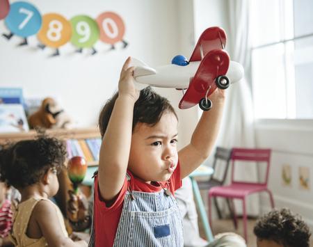 Bambino in età prescolare che si diverte a giocare con il suo aeroplano giocattolo