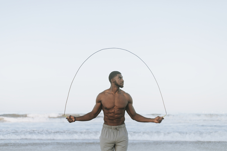 Fit man jumping rope at the beach Standard-Bild