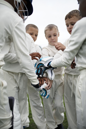 Young cricketer stacking their hands together